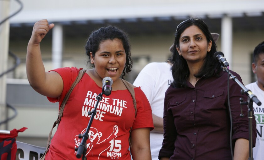 Seattle City Council Member Kshama Sawant, right, looks on as Stephanie Sucasaca holds up a fist as Sawant had just done while interpreting Sawant's remarks into Spanish on May Day.