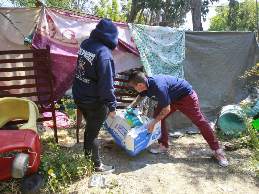 Volunteers for the Alpha Project deliver food supplies to an encampment in an area near the Plaza Bonita Mall.