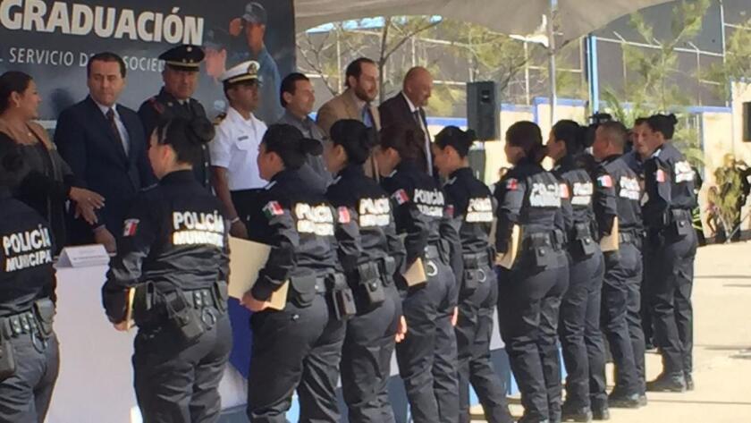 El pasado miércoles, en la ciudad fronteriza de Tecate, México, nuevos graduados de la policía de Baja California -Academia de Seguridad Pública del Estado- aceptan sus diplomas (Robin Abcarian / Los Angeles Times).