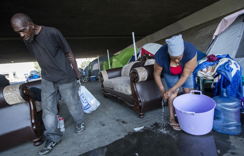 Sharrell Williams, 52, right, prepares to do her laundry at the homeless encampment in Pacoima.
