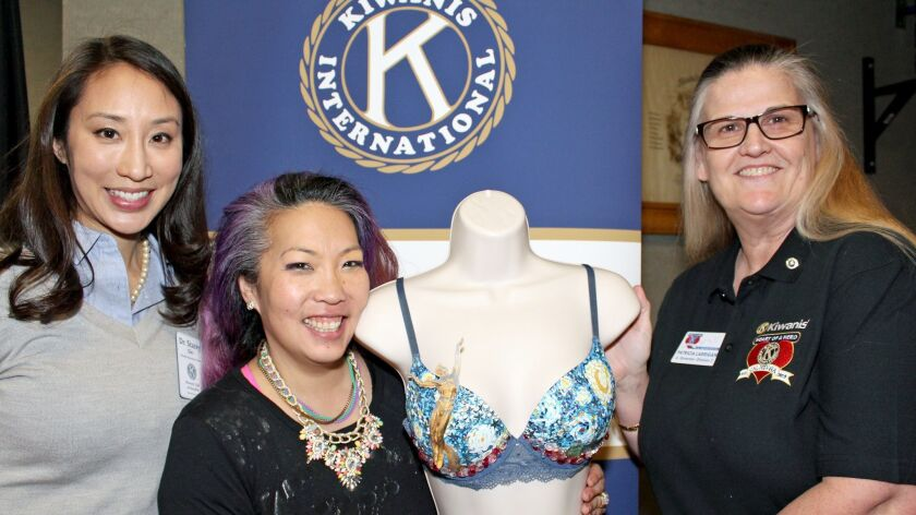 Susan Jekarl shows off her decorated bra at Glendale Kiwanis. Surrounding her is Stacey Gin Nishi,