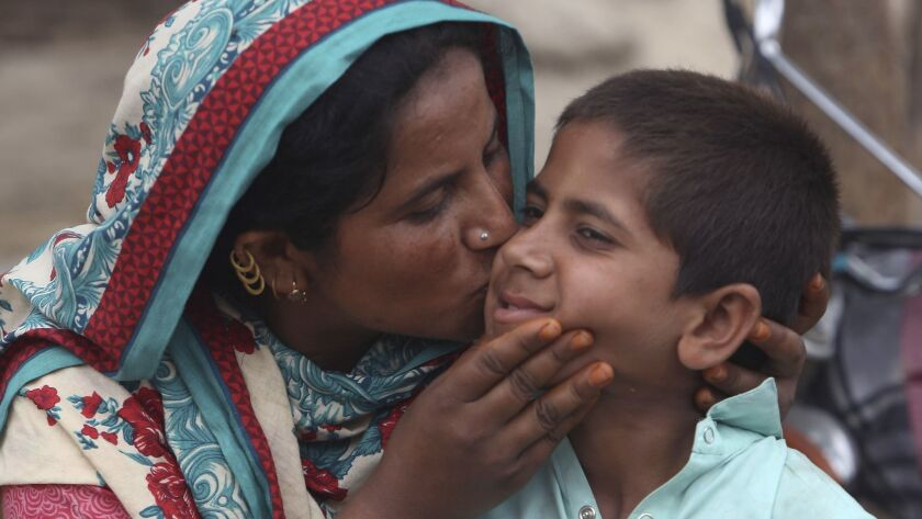 A Pakistani mother kisses her son Ali Raza, 10, infected with HIV in a village near Ratodero, a smal