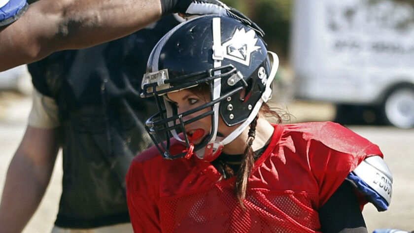 Jen Welter is congratulated by a teammate during a team practice session with the Texas Revolution in February 2014.