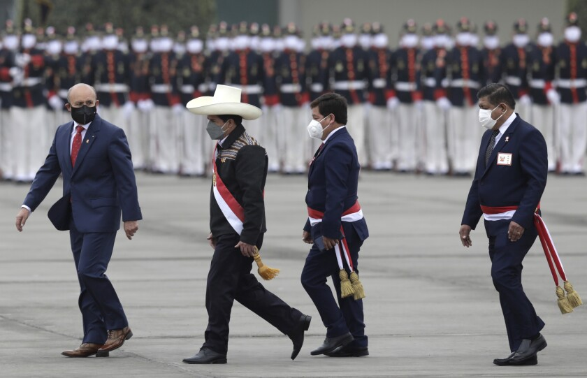 Peru's President Pedro Castillo, second from left, is followed by Prime Minister Guido Bellido and Defense Minister Walter Ayala at a military parade in Lima, Peru, Friday, July 30, 2021. (AP Photo/Guadalupe Pardo)