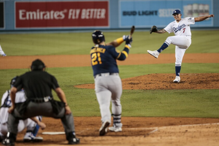 Julio Urias completes a pitch and Brewers first baseman Daniel Vogelbach swings and misses.