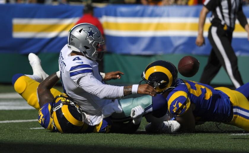 Rams linebackers  Natrez Patrick, left, and Bryce Hager sack Cowboys quarterback Dak Prescott.