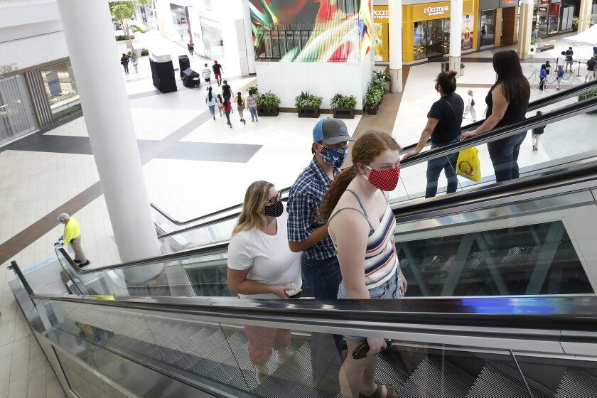 People wearing masks take an escalator