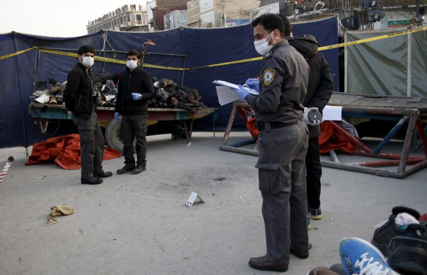 Pakistani investigators examine the site of a bomb explosion, in Rawalpindi, Pakistan, Sunday, Dec. 13, 2020. The roadside bomb exploded near a police station in the Pakistani garrison city of Rawalpindi on Sunday, wounding many people, police said. (AP Photo/A.H. Chaudary)