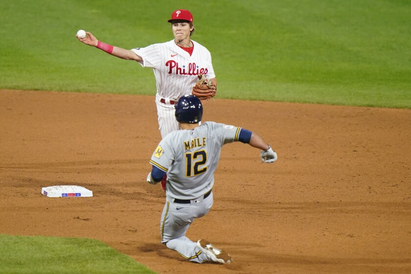 Philadelphia Phillies second baseman Nick Maton, top, throws to first after forcing out Milwaukee Brewers' Luke Maile at second on a double play hit by Tyrone Taylor during the sixth inning of baseball game, Wednesday, May 5, 2021, in Philadelphia. (AP Photo/Matt Slocum)