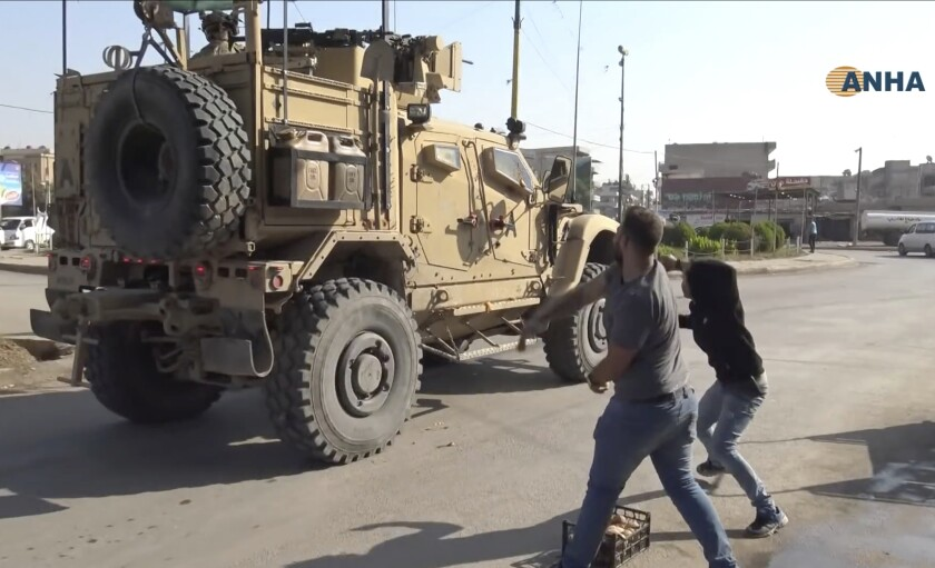 In this frame grab from video provided by Hawar News, ANHA, the Kurdish news agency, residents who are angry over the U.S. withdrawal from Syria hurl potatoes at American military vehicles in the town of Qamishli, northern Syria, on Monday.