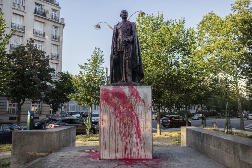 The statue of Hubert Lyautey, who served in Morocco, Algeria, Madagascar and Indochina when they were under French control, is offered with red painting Monday, June 22, 2020. Two statues related to France's colonial era were covered in graffiti Monday amid a global movement to take down monuments to figures tied to slavery or colonialism. (AP Photo/Rafael Yaghobzadeh)