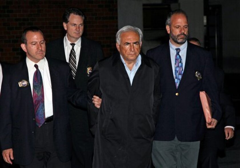 "FILE - In this May 15, 2011 file photo, Dominique Strauss-Kahn, head of the International Monetary Fund, is lead from a police station in New York where he was being held. While American authorities have condoned, or at least tolerated, such ""perp walks"" for more than a century, in France it's been"