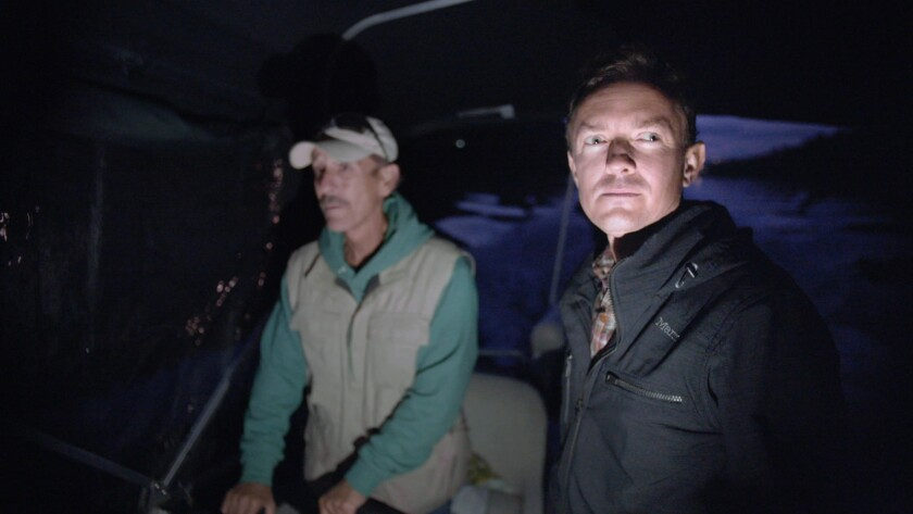 """Cullen Hoback (right) and the captain of the boat travel upstream in a scene from the movie """"What Li"""