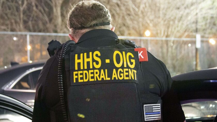 An agent with the U.S. Department of Health and Human Services' inspector general's office takes part in arrests Tuesday in Queens, N.Y., related to a Medicare scheme.