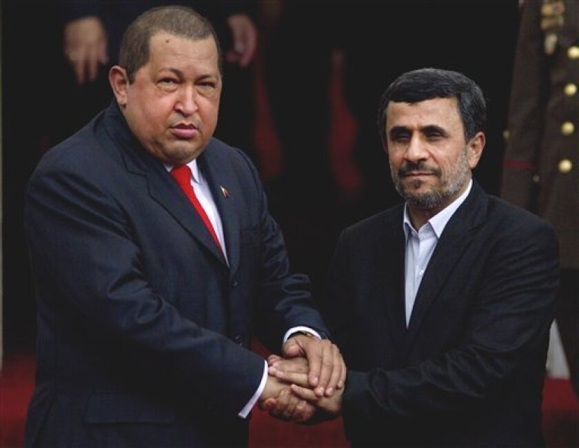 Venezuela's President Hugo Chavez, left, and Iran's President Mahmoud Ahmadinejad hold hands during a welcoming ceremony at the Miraflores presidential palace in Caracas, Venezuela, Monday Jan. 9, 2012. Ahmadinejad visited with Chavez as tensions rose with the U.S. over Tehran's nuclear program and a death sentence against an American man convicted of working for the CIA. Venezuela is the first leg of a four-nation tour that will also take Ahmadinejad to Nicaragua, Cuba and Ecuador. (AP Photo/Ariana Cubillos)