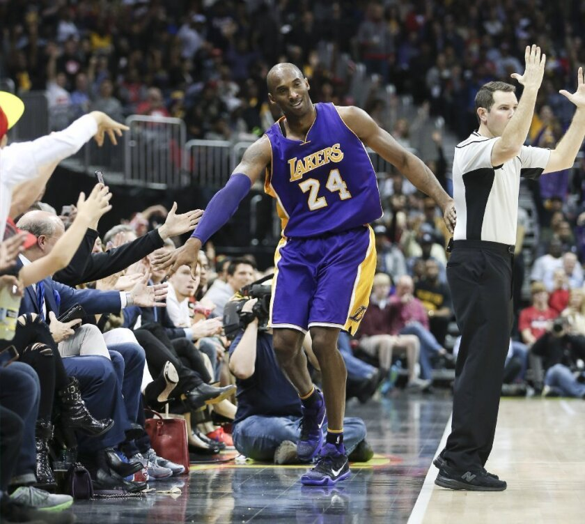 Kobe Bryant high-fives some fans during the Lakers' 100-87 loss to the Atlanta Hawks on Dec. 4.