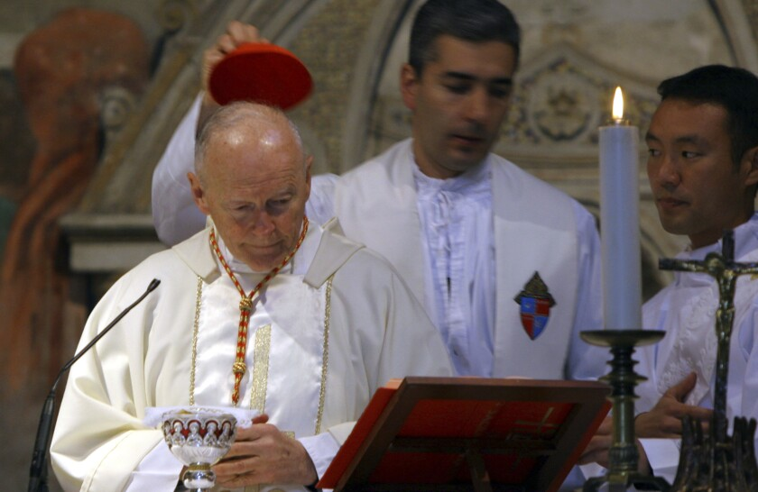 FILE - In this April 14, 2005 file photo, an aide covers the head of Washington, D.C. Cardinal Theodore McCarrick during a Mass in St. Nereus and Achilleus Church in Rome. On Tuesday, Nov. 10, 2020, the Vatican is taking the extraordinary step of publishing its two-year investigation into the disgraced ex-Cardinal McCarrick, who was defrocked in 2019 after the Vatican determined that years of rumors that he was a sexual predator were true. (AP Photo/ Alessandra Tarantino, File)