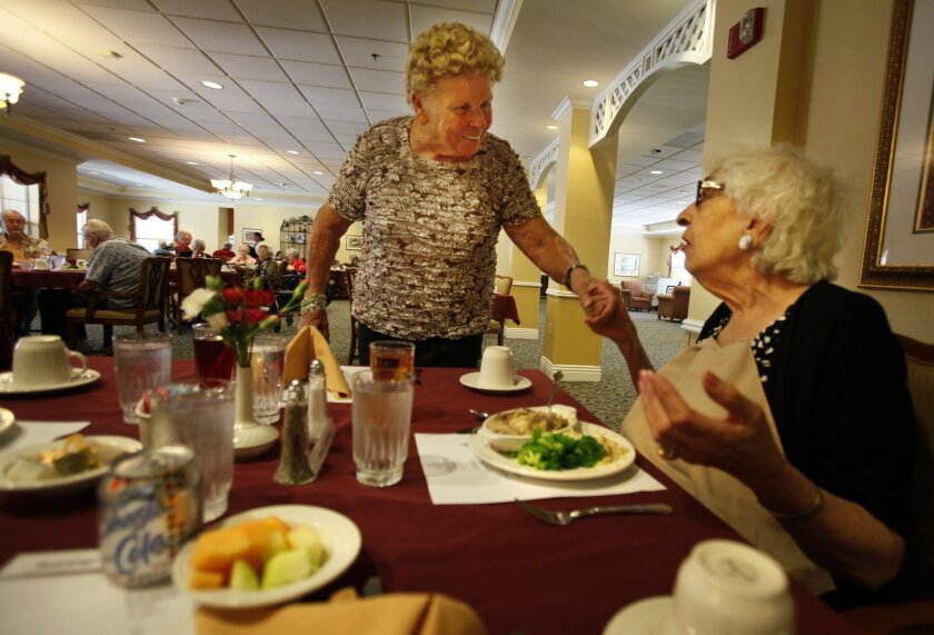 Jeanne Brown comes to the table at lunch and greets her table companion Ruth Steinberg, right, at Emeritus at Carmel Valley.