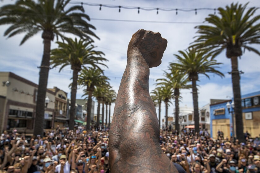 A demonstrator raises a fist at a protest at the Hermosa Beach Pier