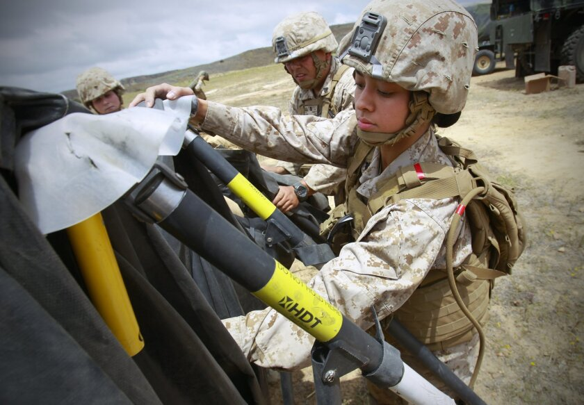 Marine Corps Cpl. Donna Gogo, an administrative specialist  with the 2nd Battalion, 11th Marine Regiment at Camp Pendleton, helps dismantle a portable tent with fellow Marines, 2nd Lt. Rosemary Doyle, far left, and Cpl. Keith Barnett, center, during a field training exercise.