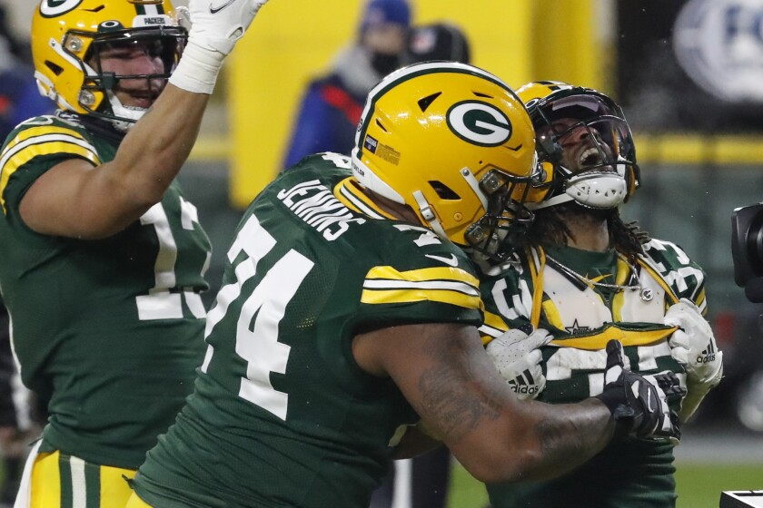 Green Bay Packers' Aaron Jones (33) celebrates his touchdown with Elgton Jenkins (74) against the Los Angeles Rams during the second half of an NFL divisional playoff football game, Saturday, Jan. 16, 2021, in Green Bay, Wis. (AP Photo/Mike Roemer)