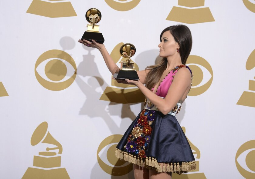 """Kacey Musgraves poses in the press room with the awards for best country album for """"Same Trailer Different Park"""" and best country song for """"Merry Go Round"""" at the 56th annual Grammy Awards at Staples Center on Sunday, Jan. 26, 2014, in Los Angeles. (Photo by Dan Steinberg/Invision/AP)"""