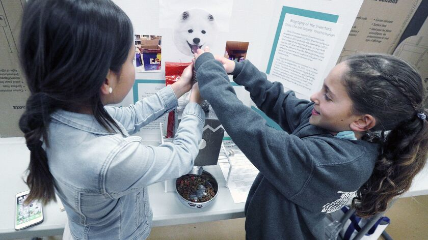 Fifth-grade students Oliva Cha and Gayané Khachaturian work together put put dog food into their inv