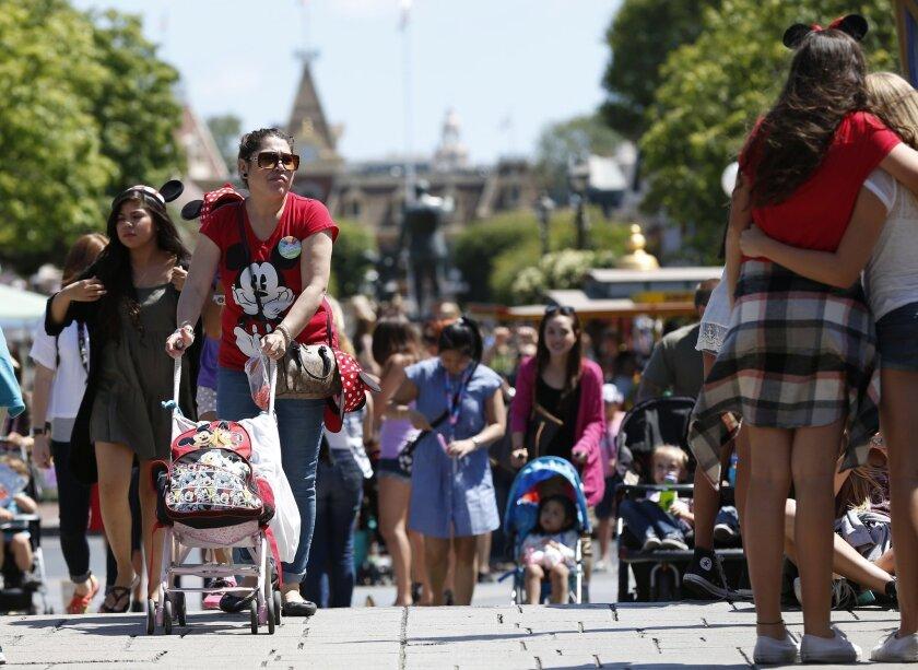 Patrons walk along Main Street in Disneyland on May 20, 2014, in Anaheim, Calif.