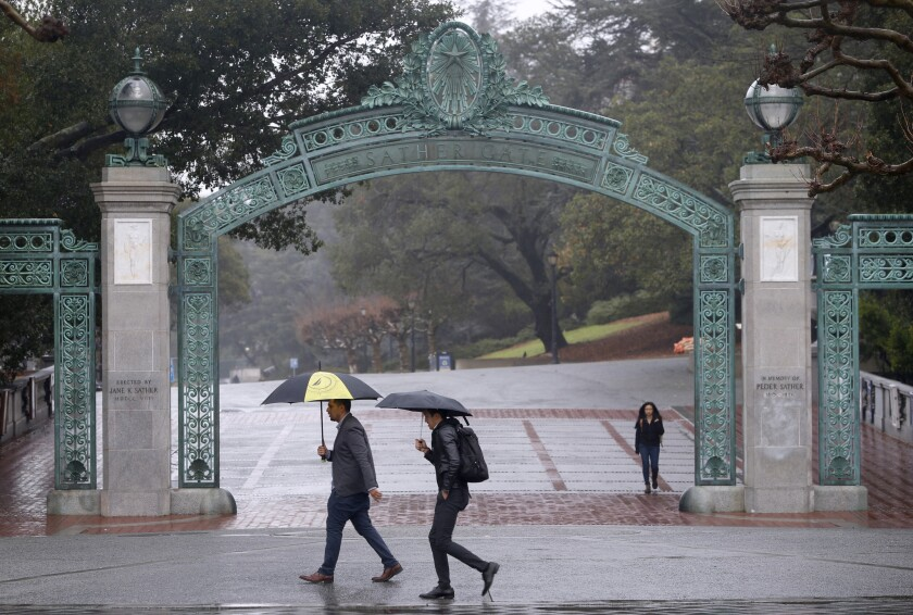 Two UC Berkeley law students are pushing a new proposed law that would automatically register college students to vote when they sign up for classes online. Here, pedestrians walk past Sather Gate on campus.