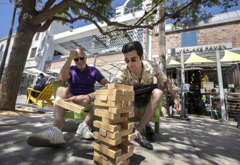Two people play giant Jenga outside an area with restaurants