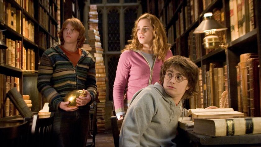 "Ron (Rupert Grint), left, Hermione (Emma Watson) and Harry (Daniel Radcliffe) research in the Hogwarts library in ""Harry Potter and the Goblet of Fire."""