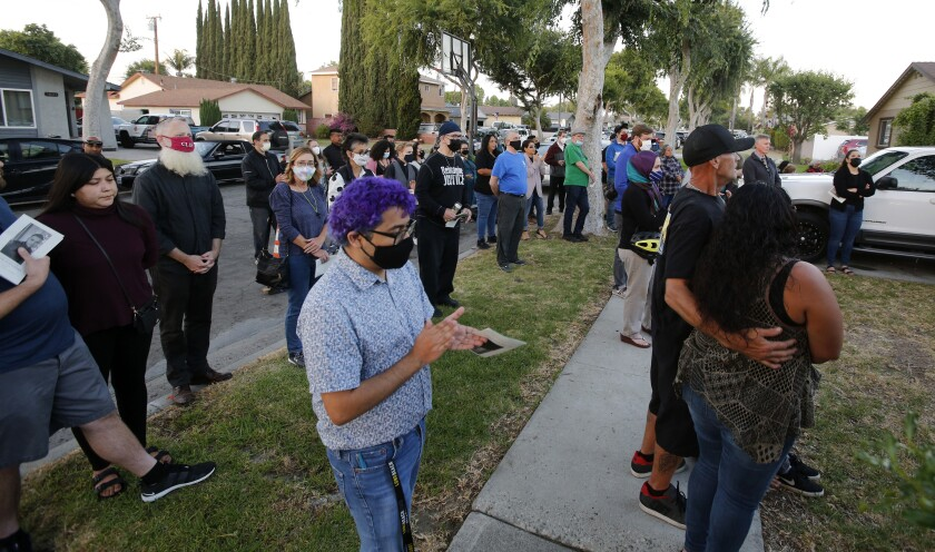 Neighbors and family members attend a memorial
