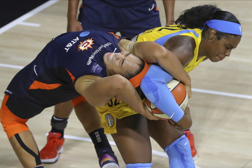 Connecticut Sun's Brionna Jones, left, reaches back to tie up a rebound with Chicago Sky's Cheyenne Parker during the second half of a WNBA basketball game Saturday, Aug. 8, 2020, in Bradenton, Fla. (AP Photo/Mike Carlson)