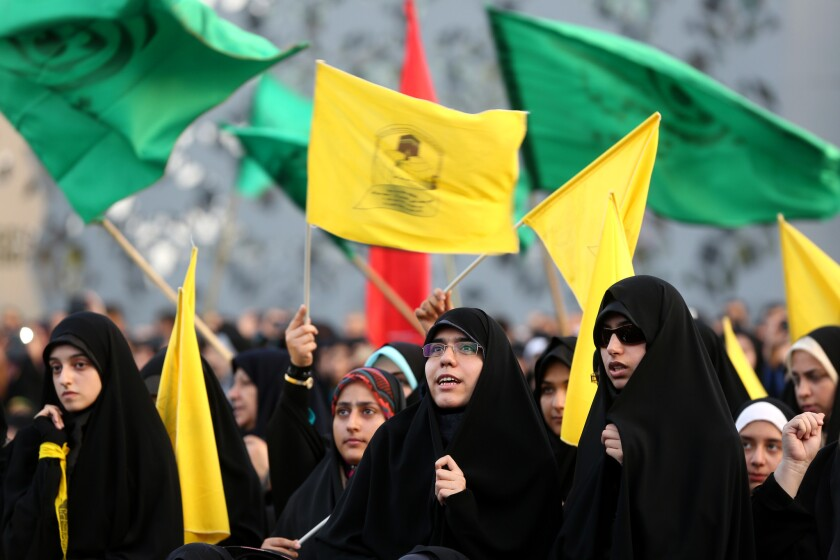 Iranian women wave Islamic flags while chanting against the militant Islamic State of Iraq and Syria movement during a rally in Tehran.