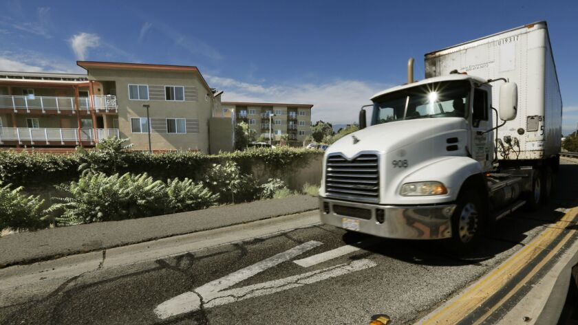 A truck exits the 710 Freeway at East Alondra Boulevard next to an apartment complex in Compton. The U.S. Environmental Protection Agency plans to update emissions standards for heavy-duty diesel trucks in an effort to reduce smog-forming pollution.