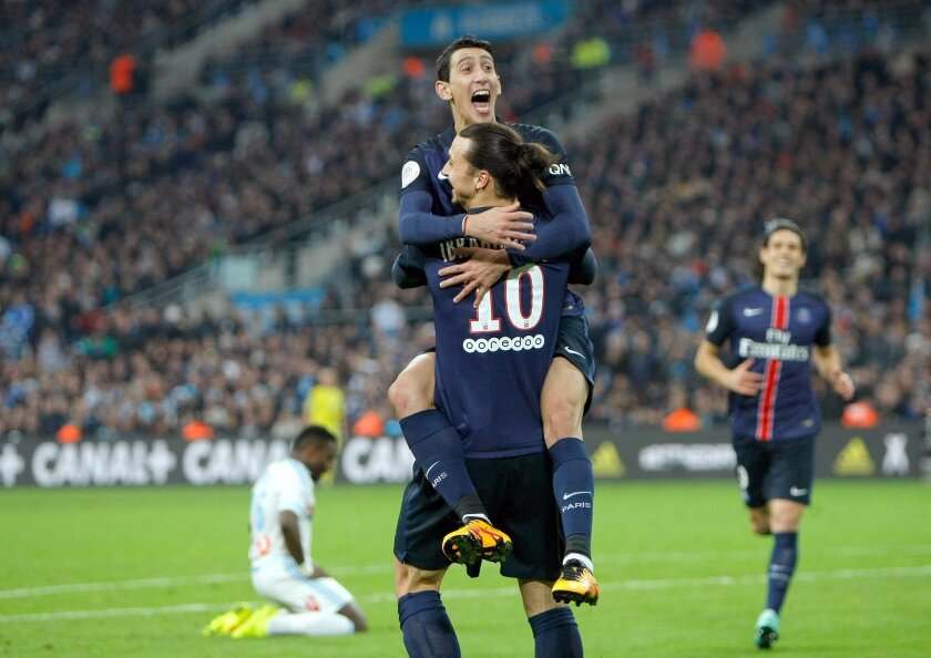 Paris Saint Germain's Angel Di Maria, top, celebrates with teammate Zlatan Ibrahimovic after scoring against Marseille, during the League One soccer match between Marseille and Paris Saint-Germain, at the Velodrome Stadium, in Marseille, southern France, Sunday, Feb. 7, 2016. (AP Photo/Claude Paris