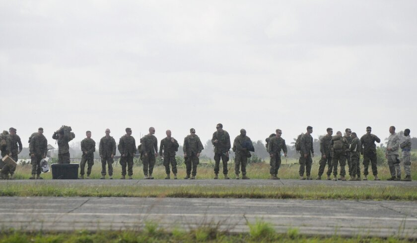 """U.S marines arrive at the Roberts International airport in Monrovia, Liberia, Thursday, Oct. 9, 2014. Six U.S. military planes arrived Thursday at the epicenter of the Ebola crisis, carrying more aid and American Marines into Liberia, the country hardest hit by the deadly disease that has devastated West Africa and stirred anxiety across a fearful world. At a World Bank meeting in Washington, the presidents of several West African countries struggling with Ebola pleaded for help, with one calling the epidemic """"a tragedy unforeseen in modern times."""" (AP Photo/Abbas Dulleh)"""