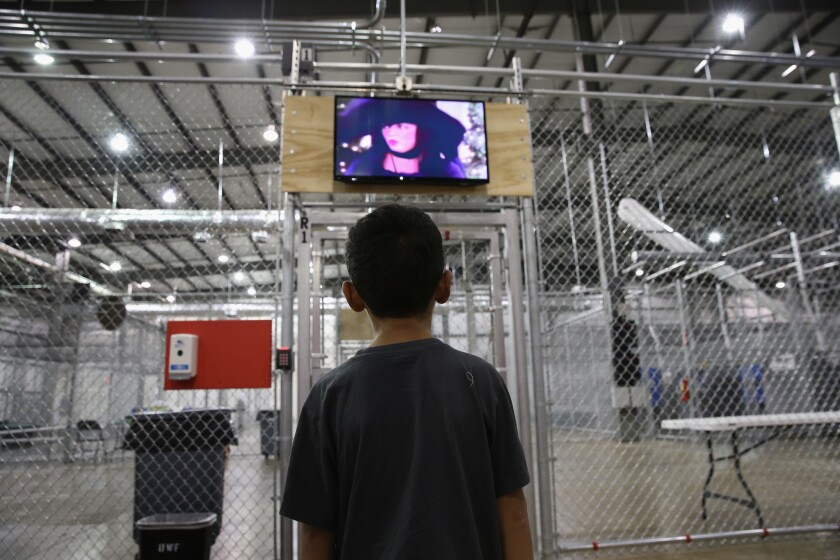 A boy from Honduras watches a movie at an immigrant detention facility in McAllen, Texas.