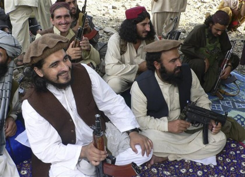 In this photo taken Sunday, Oct. 4, 2009, new Pakistani Taliban chief Hakimullah Mehsud, left, is seen with his comrade Waliur Rehman, front center, during his meeting with media in Sararogha of Pakistani tribal area of South Waziristan along the Afghanistan border. Mehsud vowed to strike back at Pakistan and the U.S. for the increasing number of drone attacks in the tribal areas along the border with Afghanistan. (AP Photo/Ishtiaq Mehsud)