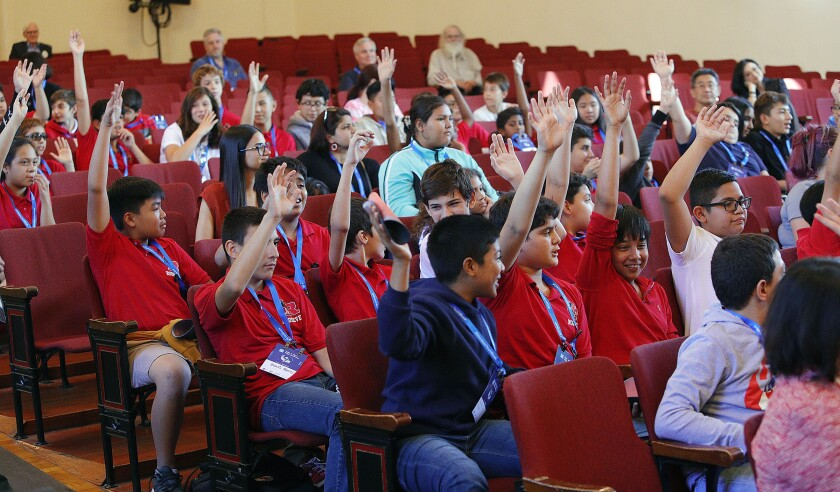 Students at Roosevelt Middle School raise their hands after being asked if any of them has done any computer programming during a panel discussion about artificial intelligence held at the campus on Sept. 16 as part of Glendale Tech Week.