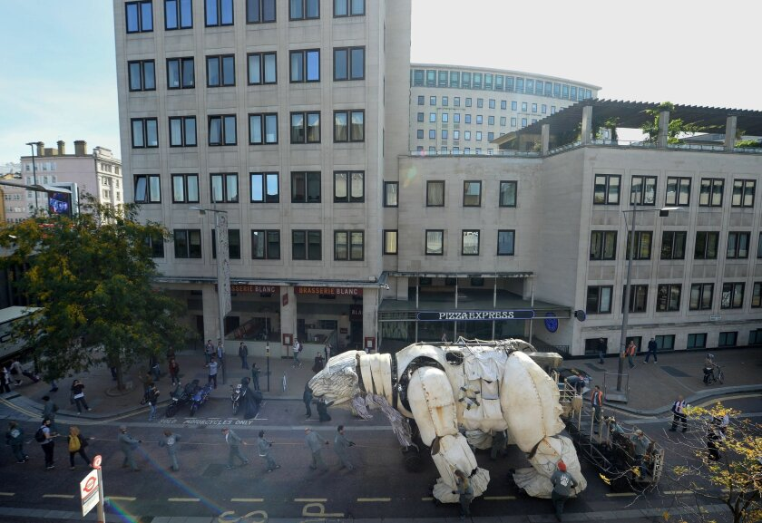 Puppeteers transport Aurora, the double decker bus sized polar bear, from in front of Shell HQ in London as Greenpeace activists celebrate Royal Dutch Shell's decision to stop Arctic oil drilling. Tuesday Sept. 29, 2015. Now Shell has announced its Arctic exit, the bear will be transported to Paris where the nations of the world will soon gather to negotiate a deal on climate change. See PA story ENVIRONMENT Shell. (Anthony Devlin/PA via AP) UNITED KINGDOM OUT