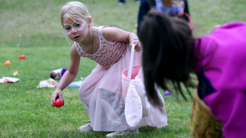 Brooke Coupe, 3 of Huntington Beach, gathers up candy and Easter eggs at the Easter Egg hunt during