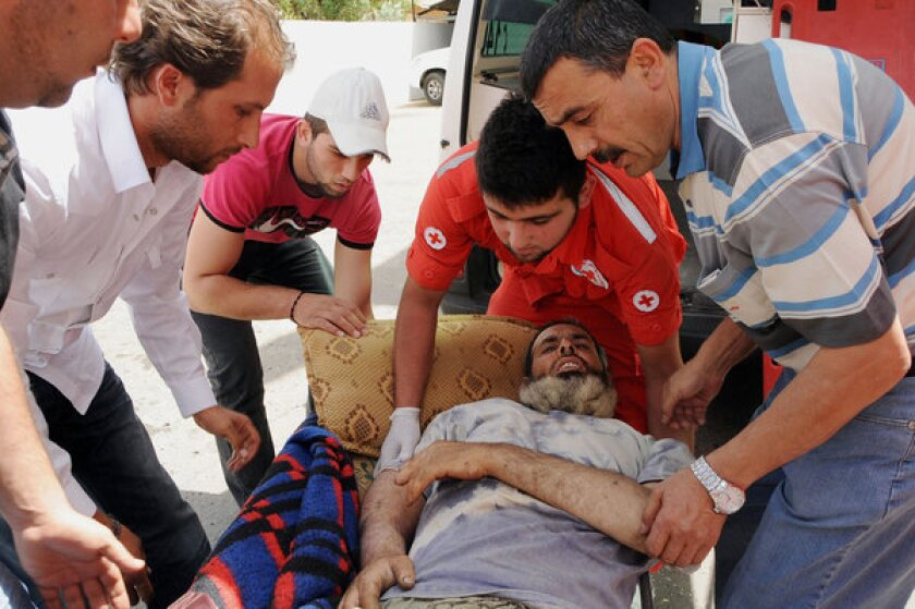 Members of the Lebanese Red Cross carry a man who was injured in fighting in the Syrian town of Qusair into a hospital in the Bekaa Valley.