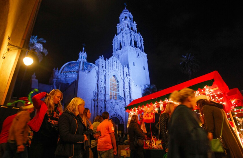 With the Museum of Man in the background, people shop at booths during December Nights at Balboa Park in San Diego. (Hayne Palmour IV)