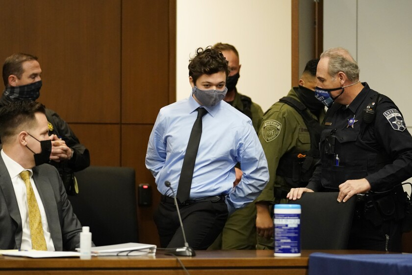 Teenager Kyle Rittenhouse, in collared shirt and tie, walks with his hands cuffed to a seat in court