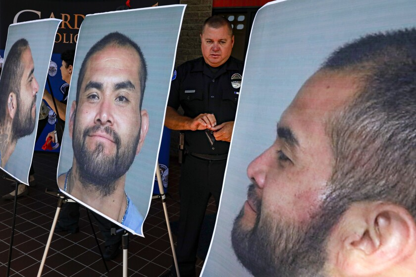 Charles Starnes stands among photographs Wednesday of Zachary Castaneda, the suspect in a deadly rampage in Orange County. Castaneda, of Garden Grove, is accused of stabbing four people to death.