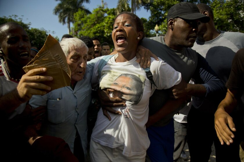 A member of the dissident group, Ladies in White, is detained by Cuban security before the start of a march marking International Human Rights Day in Havana, Cuba, Tuesday, Dec. 10, 2013. Government agents detained about 20 people arriving for the march, halting the demonstration before it started.