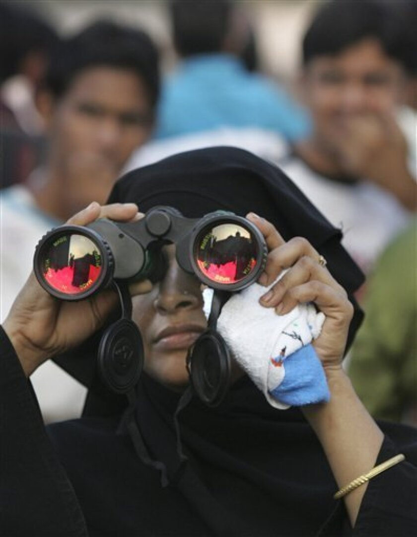 A Muslim woman looks at the damaged Taj Mahal hotel through binoculars in Mumbai, India, Wednesday, Dec.10, 2008. The Taj Mahal hotel is one of the two hotels attacked by terrorists on Nov. 26, 2008. (AP Photo/Manish Swarup)