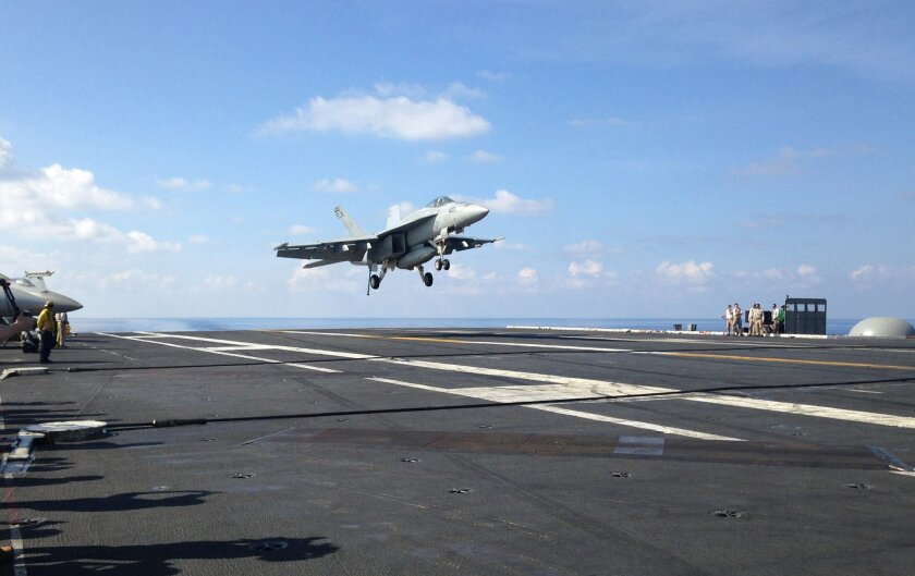FILE - In this Friday, April 15, 2016 file photo, an FA-18 jet fighter lands on the USS John C. Stennis aircraft carrier in the South China Sea while U.S. Defense Secretary Ash Carter visited the aircraft carrier during a trip to the region. American ships and fighter jets maneuvering across the So