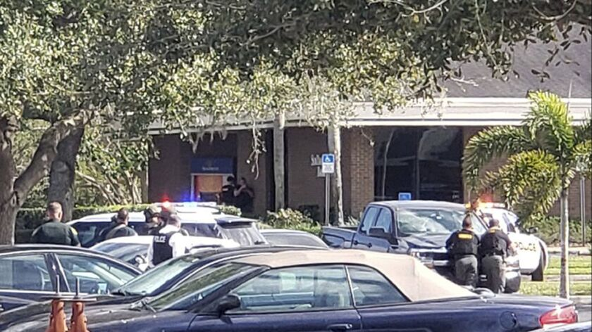 Law enforcement officials take cover outside a SunTrust Bank in Sebring, Fla., on Wednesday.